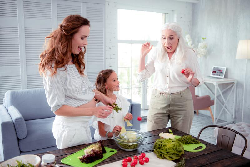 Grandmother and mother laughing after throwing little tomato into bowl. Throwing little tomato. Grandmother and mother laughing after throwing little tomato into stock photography