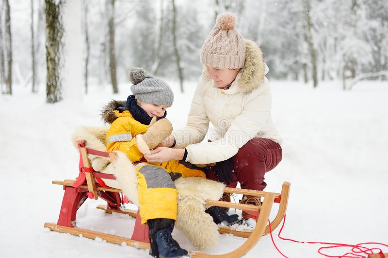 Grandmother / nanny / mother puts on a mitten to a small child during sledding in winter park. Family winter activities outdoors stock images