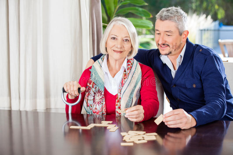 Grandmother Playing Dominoes With Grandson At stock photo