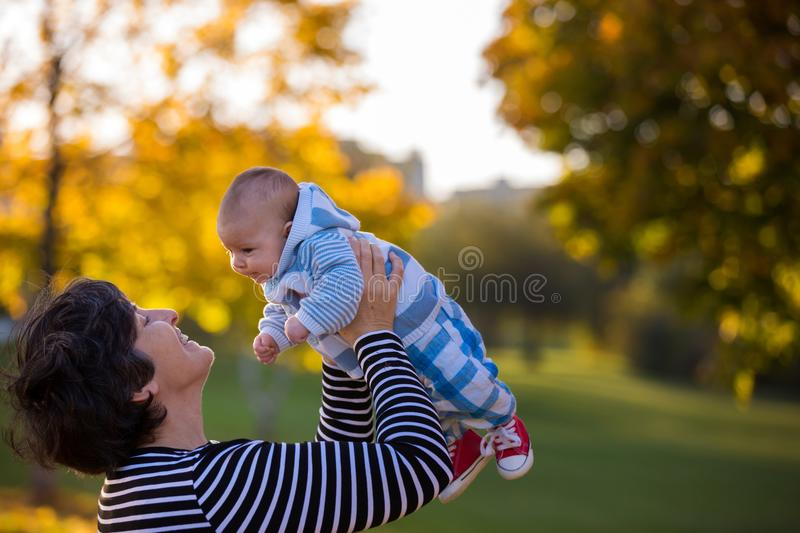 Grandmother playing in the park with her newborn baby grandchild royalty free stock image