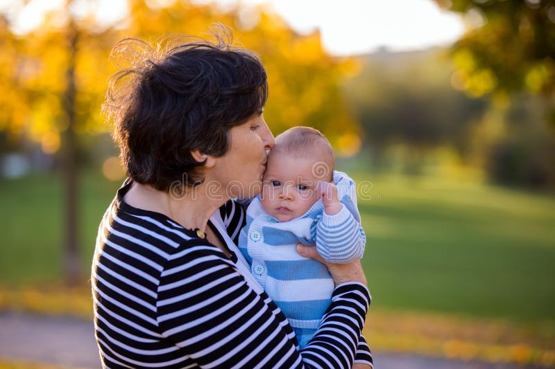 Grandmother playing in the park with her newborn baby grandchild stock photos