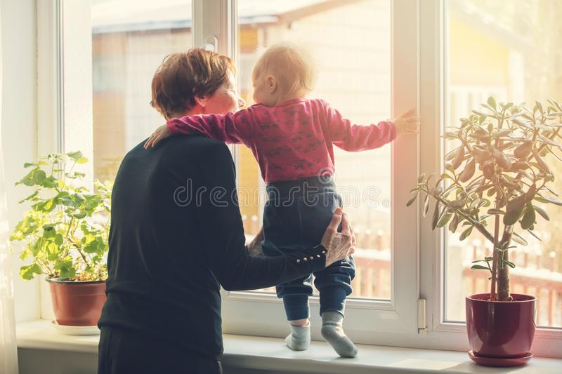 Grandmother playing and taking care of child. At home royalty free stock image