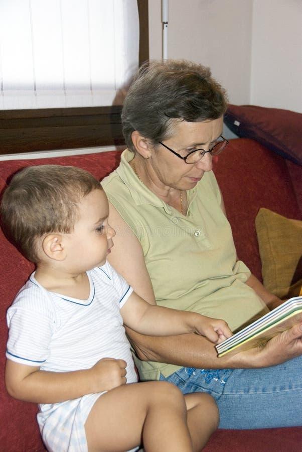 Grandmother reading book to baby stock photos