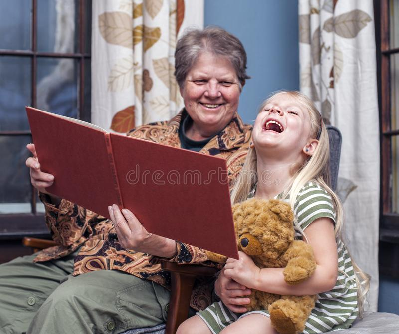 Story for night. Grandmother reading night story to her granddaughter at home stock photo