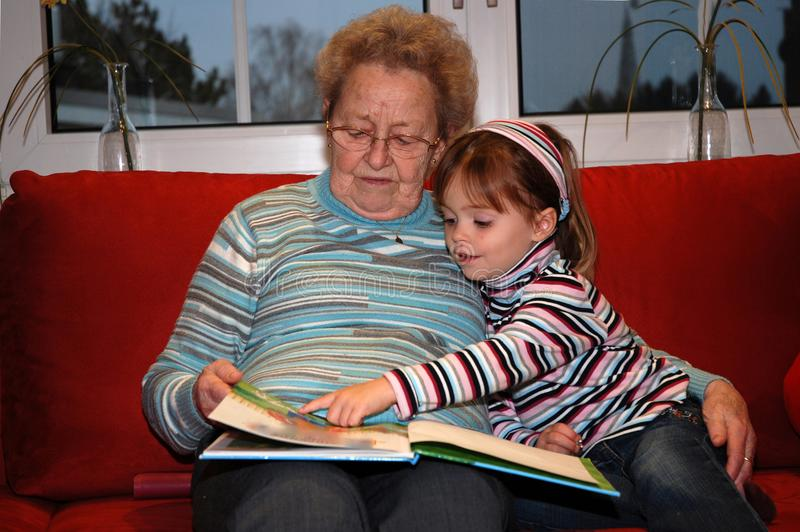 Grandmother reads a book with her little granddaughter. Great grandma snuggles with her little granddaughter, while reading a book and looking the pictures royalty free stock photo