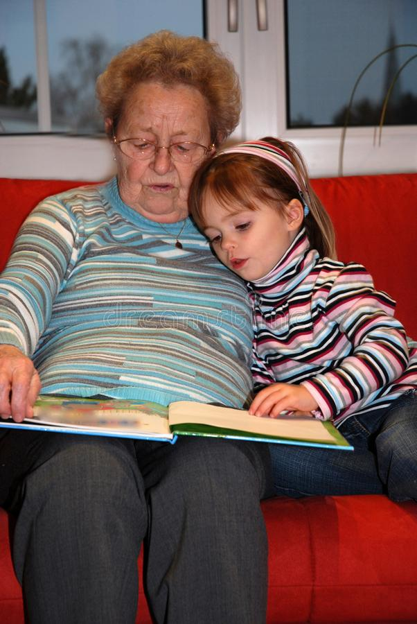 Grandmother reads a book with her little granddaughter. Great grandma snuggles with her little granddaughter, while reading a book and looking the pictures royalty free stock image