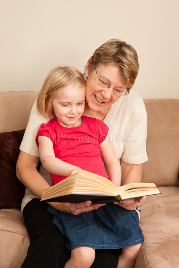 A grandmother reads to her young grand-daughter