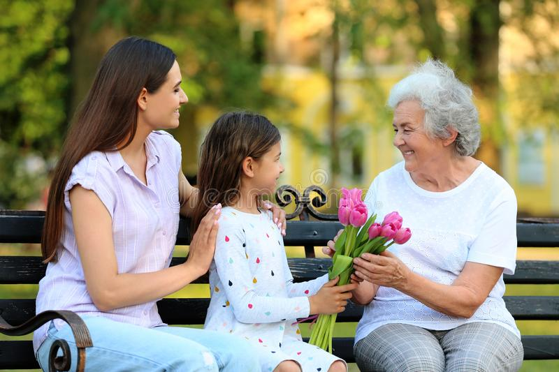 Grandmother receiving bouquet of flowers from her family on bench royalty free stock image