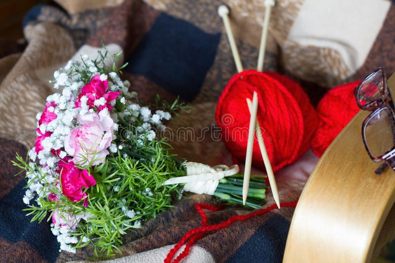 Grandmother`s day concept with flowers and knitting on armchair. Abstract stock photos