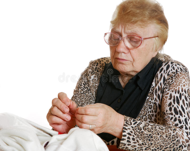 Grandmother sewing needle and thread stock photo