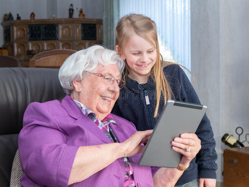 Grandmother showing something funny to her grandchild on her tab royalty free stock image