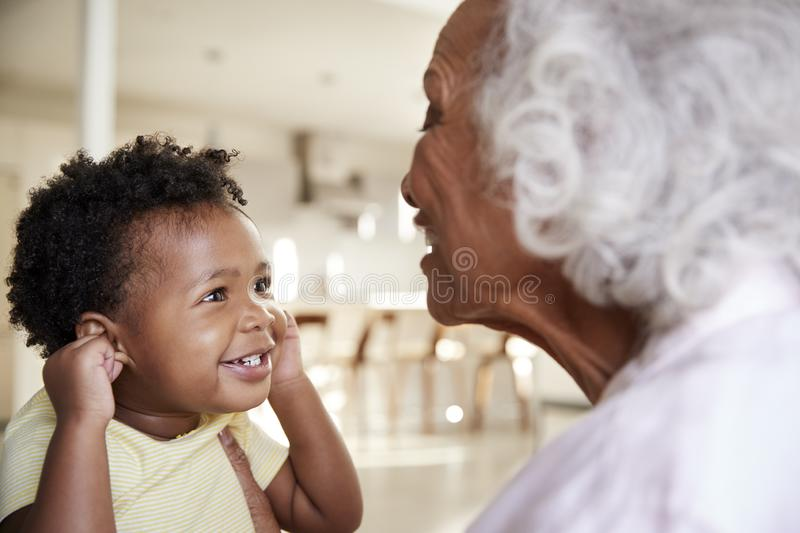 Grandmother Sitting On Sofa At Home With Baby Granddaughter Playing Game Together stock photos