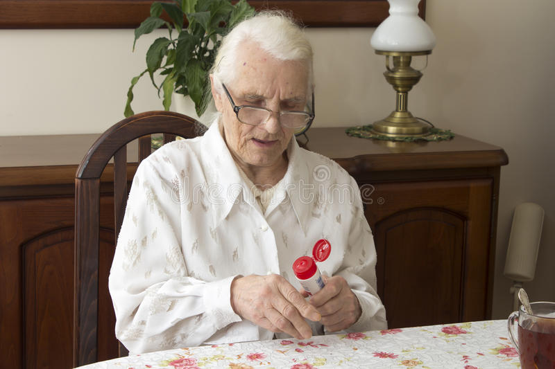 Grandmother sitting at a table in the living room and lubricates hand salve. stock photography