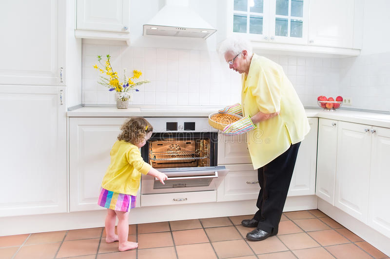 Grandmother and sweet girl baking pie in white kitchen. Happy beautiful great grandmother and her adorable granddaughter, curly toddler girl in colorful dress stock photos