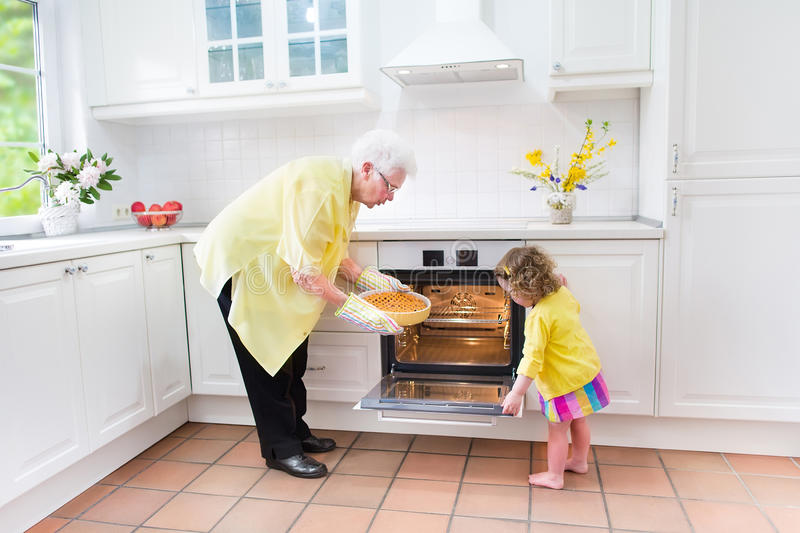 Grandmother and sweet girl baking pie in white kitchen. Happy beautiful great grandmother and her adorable granddaughter, curly toddler girl in colorful dress stock photography