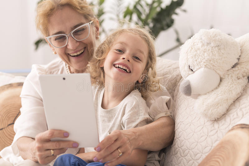 Grandmother taking selfie with child. Smiled grandmother taking the common selfie with a child, using a tablet royalty free stock photos
