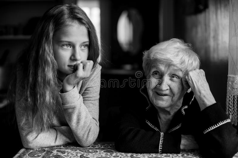 Grandmother talking with her granddaughter. Grandmother talking with her granddaughter, black-and-white photo royalty free stock image