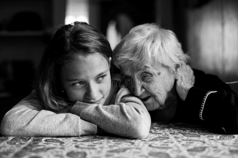 Grandmother talking with her granddaughter, tenderness. Black-and-white photo stock image