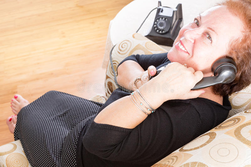Grandmother talking on a retro rotary phone. Grandmother relaxing at home in a comfy armchair in a stylish black dress and bare feet talking on a retro rotary royalty free stock photo