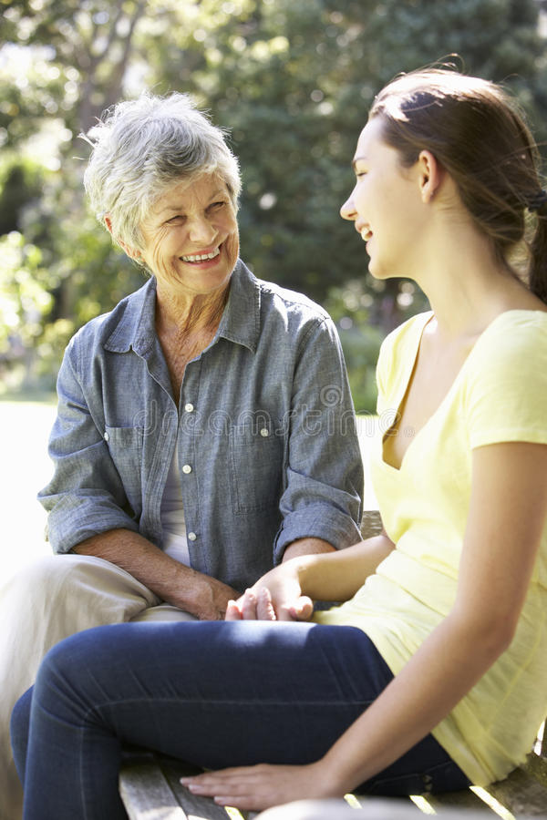 Grandmother Talking With Teenage Granddaughter On Bench stock photo