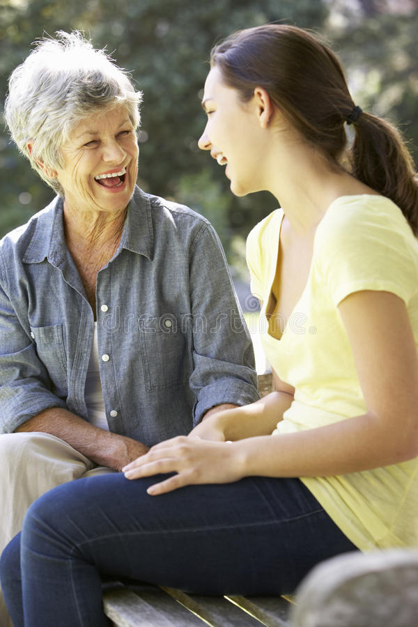 Grandmother Talking With Teenage Granddaughter On Bench stock images