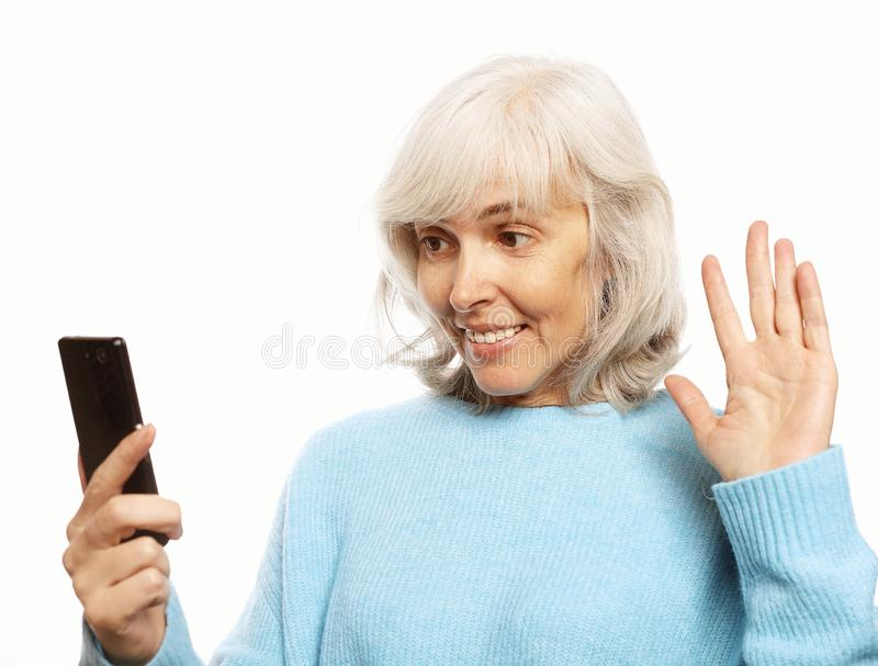 Grandmother is talking to her grandchildren by phone. Lifestyle, tehnology  and people concept: grandmother is talking to her grandchildren by phone, smiling and stock images