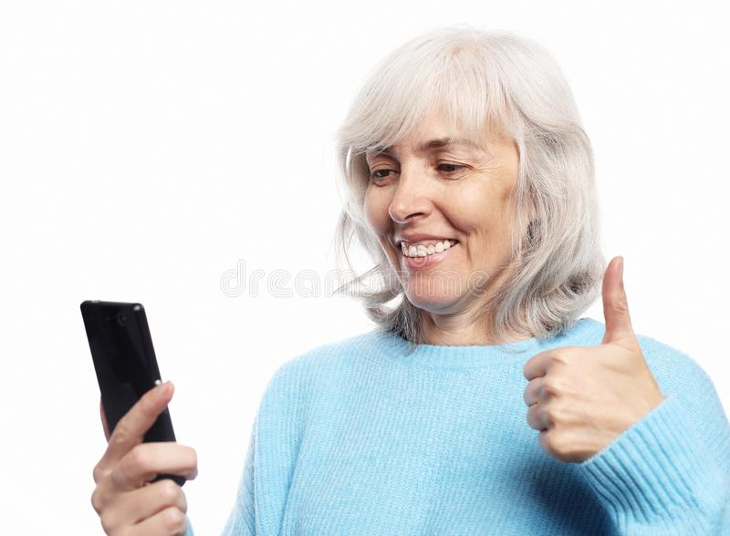 Grandmother is talking to her grandchildren by phone, smiling and greeting them. Lifestyle, tehnology  and people concept: grandmother is talking to her stock photos