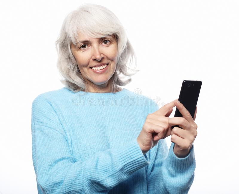 Grandmother is talking to her grandchildren by phone, smiling and greeting them. Lifestyle, tehnology and people concept: senior woman with smartphone texting royalty free stock images