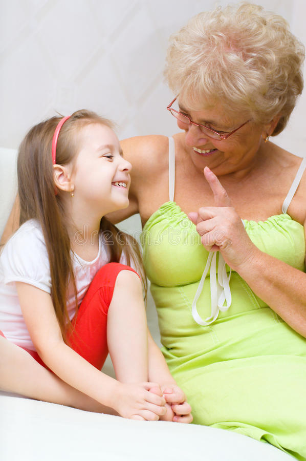 Grandmother talking to her granddaughter. Indoor shoot royalty free stock photos