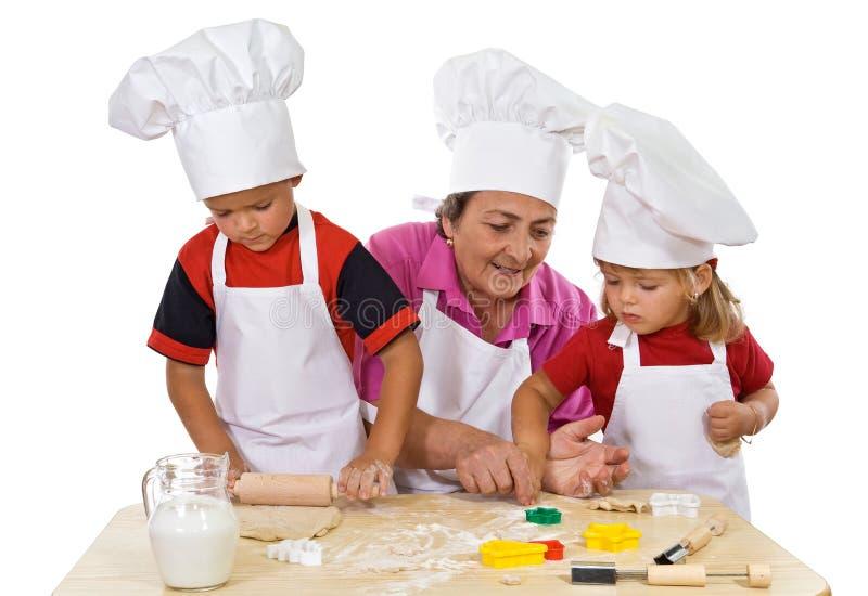 Grandmother teaching kids making cookies. Grandmother and kids making cookies series - isolated royalty free stock photo