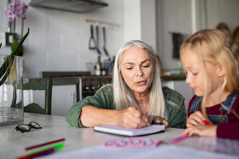 Grandmother teaching to granddaughter at home stock images