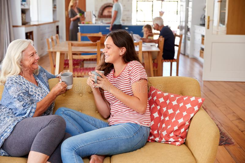 Grandmother With Teenage Granddaughter Relaxing On Sofa And Talking At Home royalty free stock image