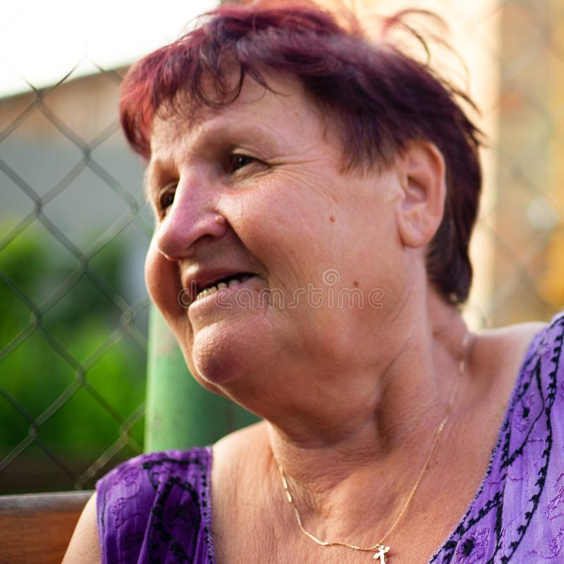 Grandmother tells a funny story from her youth, a portrait of an elderly woman 60 years old stock photo