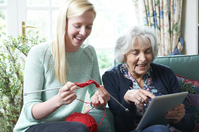 Grandmother Using Digital Tablet Whilst Granddaughter Knits. Smiling Grandmother Using Digital Tablet Whilst Granddaughter Knits royalty free stock photos