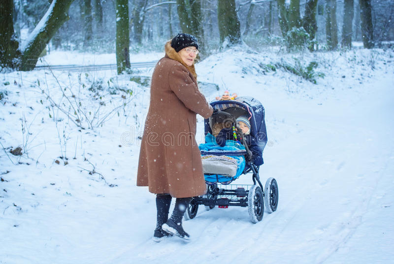 Grandmother walking with baby boy in winter royalty free stock image