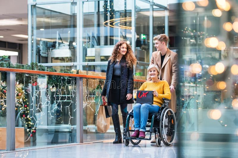 A grandmother in wheelchair and teenage grandchildren in shopping center at Christmas. stock photos