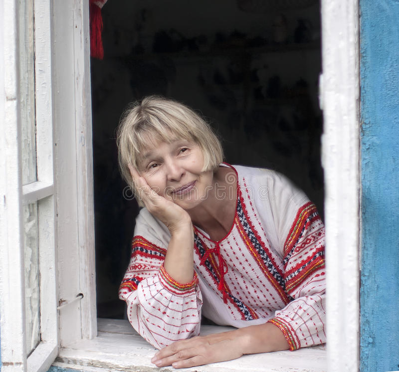 Grandmother in the window. Mature Russian peasant woman at the window of a rural house stock image