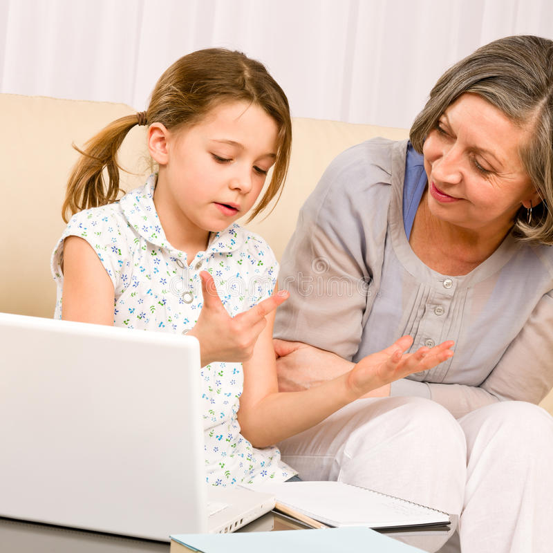 Grandmother and young girl with laptop learn count