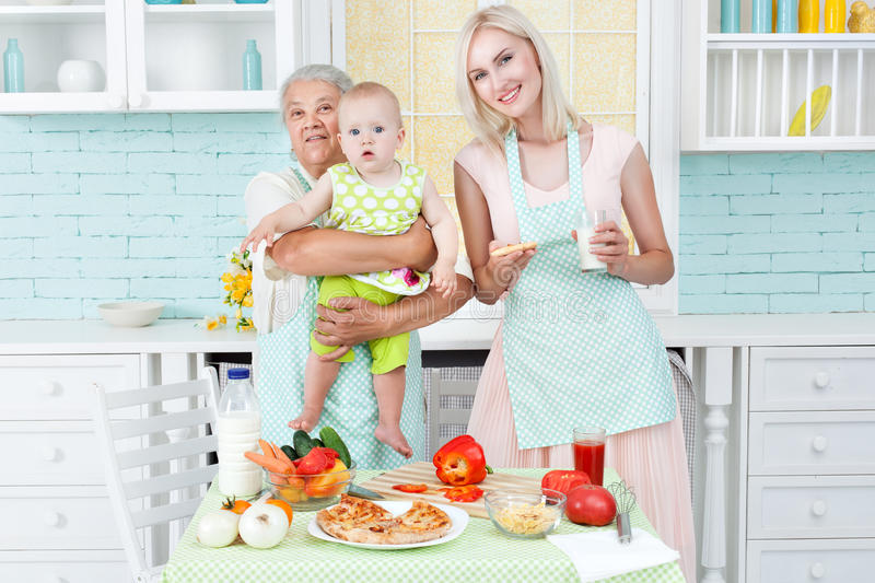 Grandmother the young girl and the small child. The grandmother the young girl and the small child in kitchen near a table on which pizza lies stock images