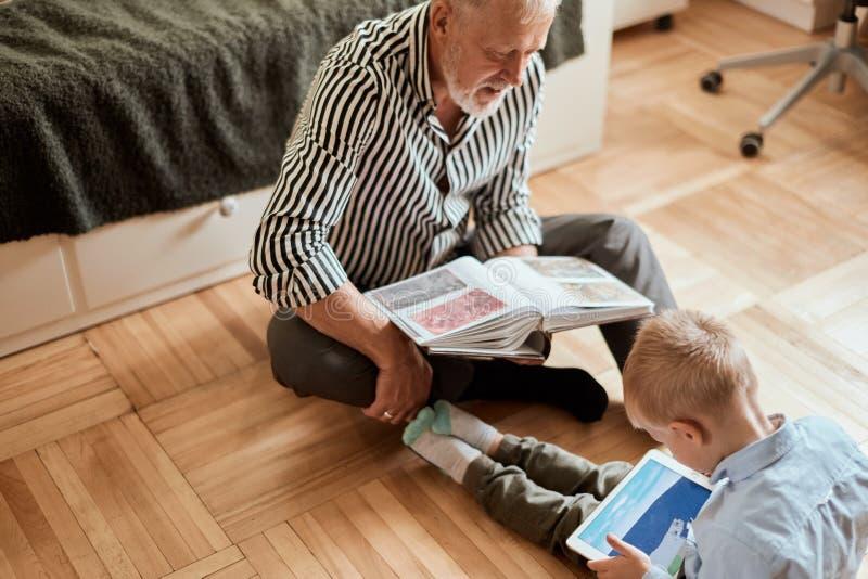 Grandpa смотрит фотоальбом с его свадьбой, мальчика используя электронную таблетку стоковая фотография rf