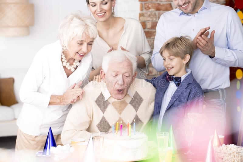 Grandpa blowing out candles on birthday cake. Grandpa blowing out candles at his birthday cake and his family watching him stock image