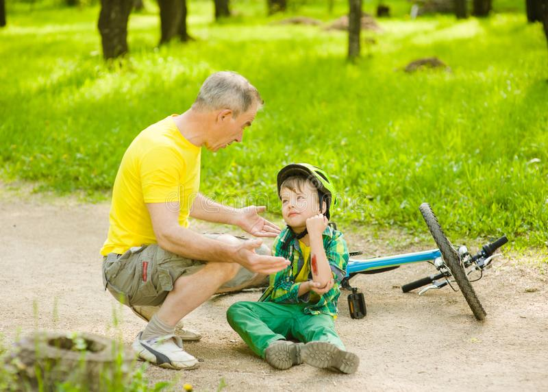 Grandpa calms grandson that fell from the bike royalty free stock photo