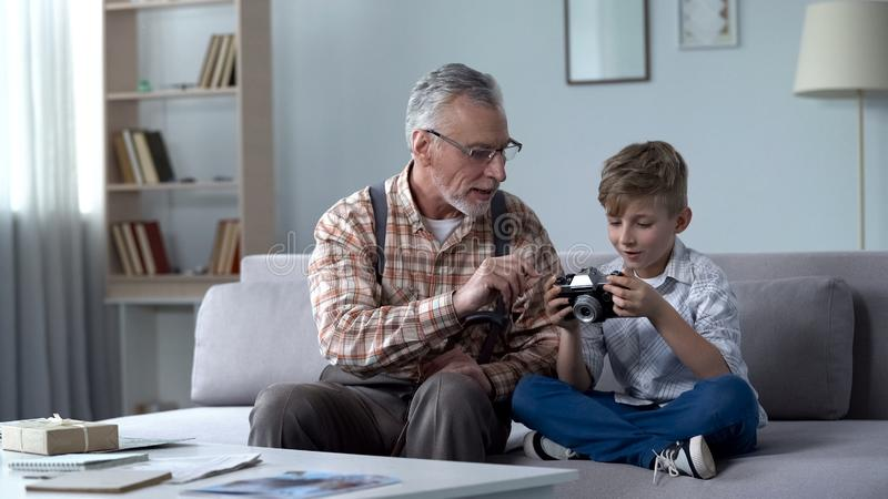 Grandpa explaining grandson how to use retro camera, young photographer dreams stock photos
