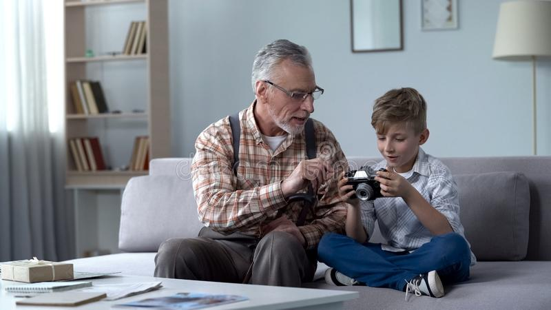 Grandpa explaining grandson how to use retro camera, young photographer dreams stock images