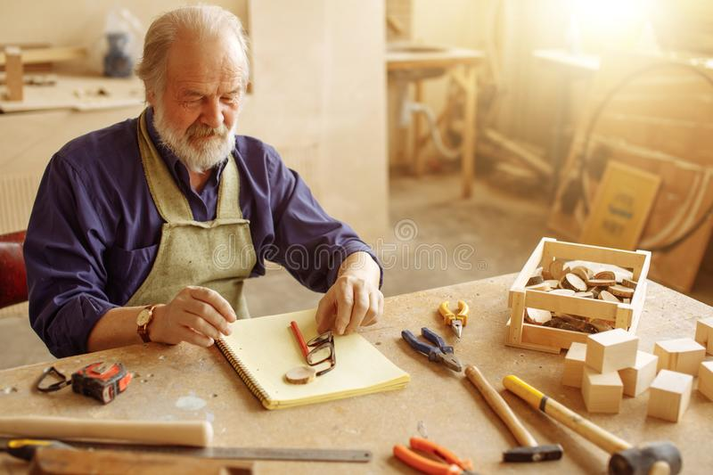 Grandpa going to take glasses to work while sitting at the table royalty free stock image