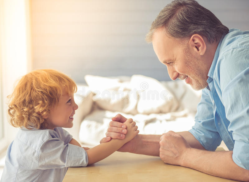 Grandpa and grandson. Handsome grandpa and grandson are wrestling and smiling while spending time together at home stock images