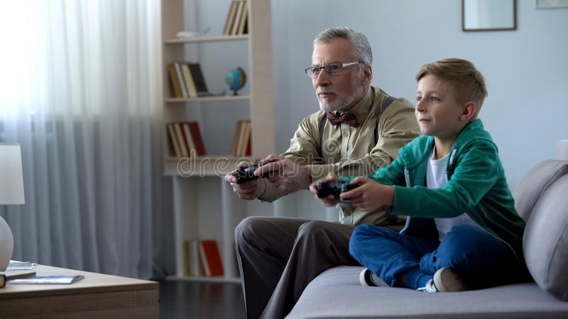 Grandpa and grandson playing video game with console, happy time together royalty free stock photo