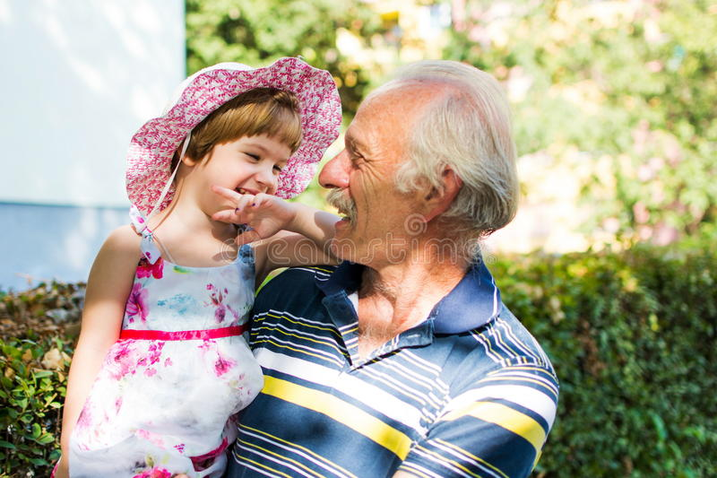 Grandpa and his granddaughter laughing outdoors stock photo