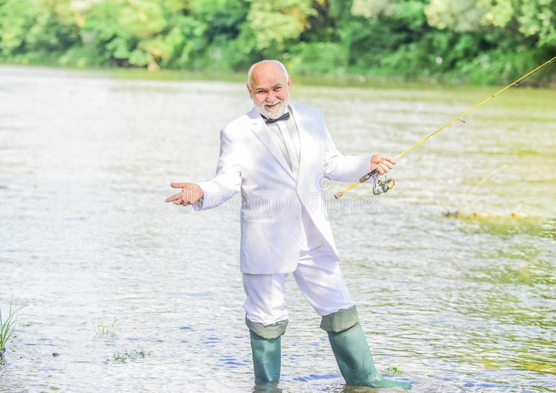 Grandpa is my name, fishing is my game. Hobby and recreation. Fisherman in formal suit. Successful catch. Senior man. Fishing. Retired businessman. Elegant royalty free stock photo