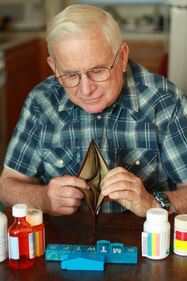 Grandpa que olha na carteira vazia imagem de stock
